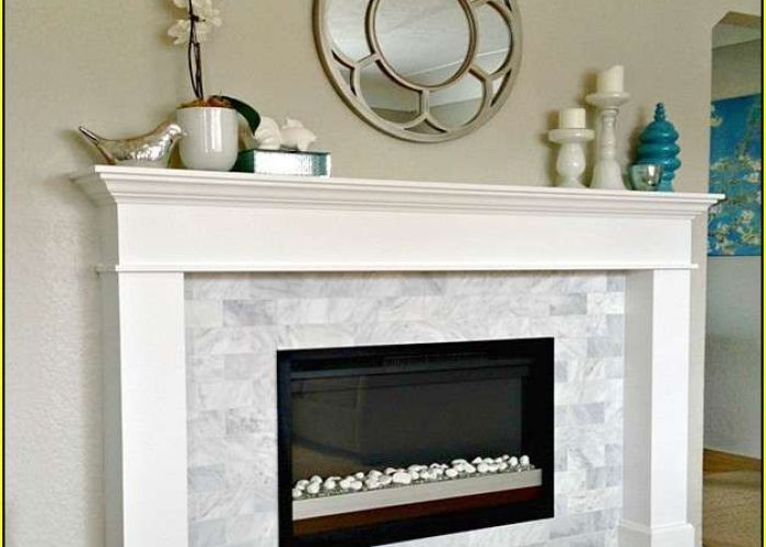 Black box fireplace with river rocks instead of glass but shows the contrast white surround also