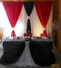 A black and red backdrop and head table design by ...