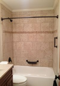 Tile tub surround. Beige tile bathtub surround with oil