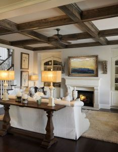 Dark wooden beams and flooring frame an elegant white wall with arched niches that flank  fireplace new homes in the kingswood community built by edward also living room is open yet comfy cozy rh pinterest