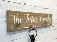 This personalized wooden key holder sign features zinc ...