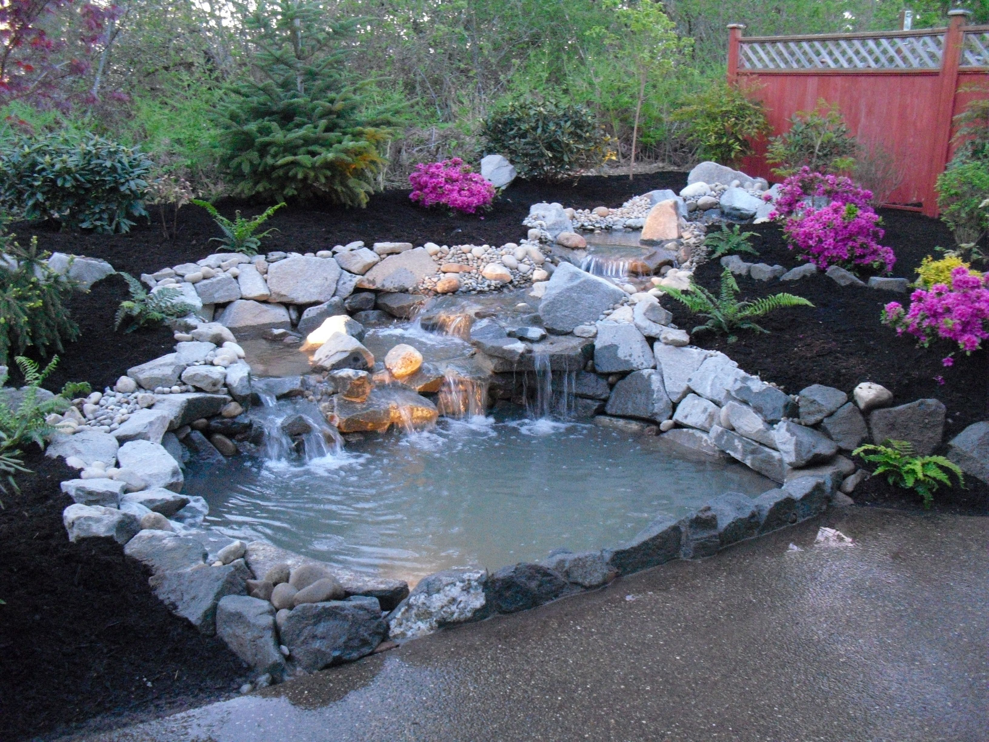 Garden Pond Design With Round Brick Pattern Tiles And Large Statue