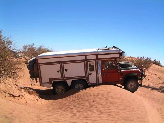 A Foley Land Rover 6x6 camper on it travels