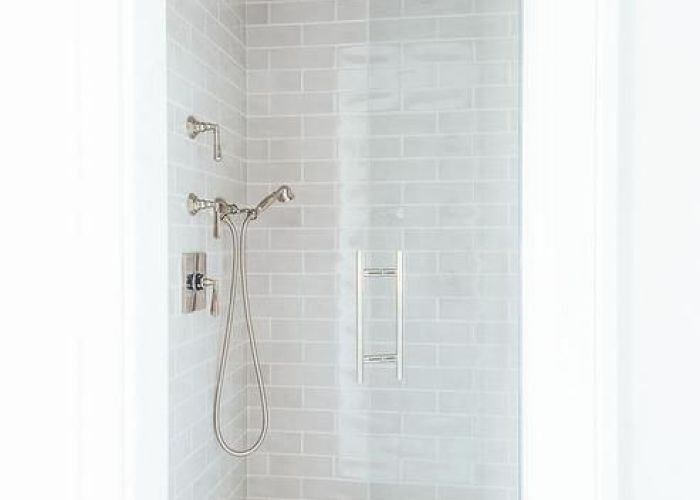 Small walk in shower features gray subway tiles on ceiling and walls lined with  hand also