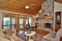 stacked stone fireplace in living room with vaulted ...