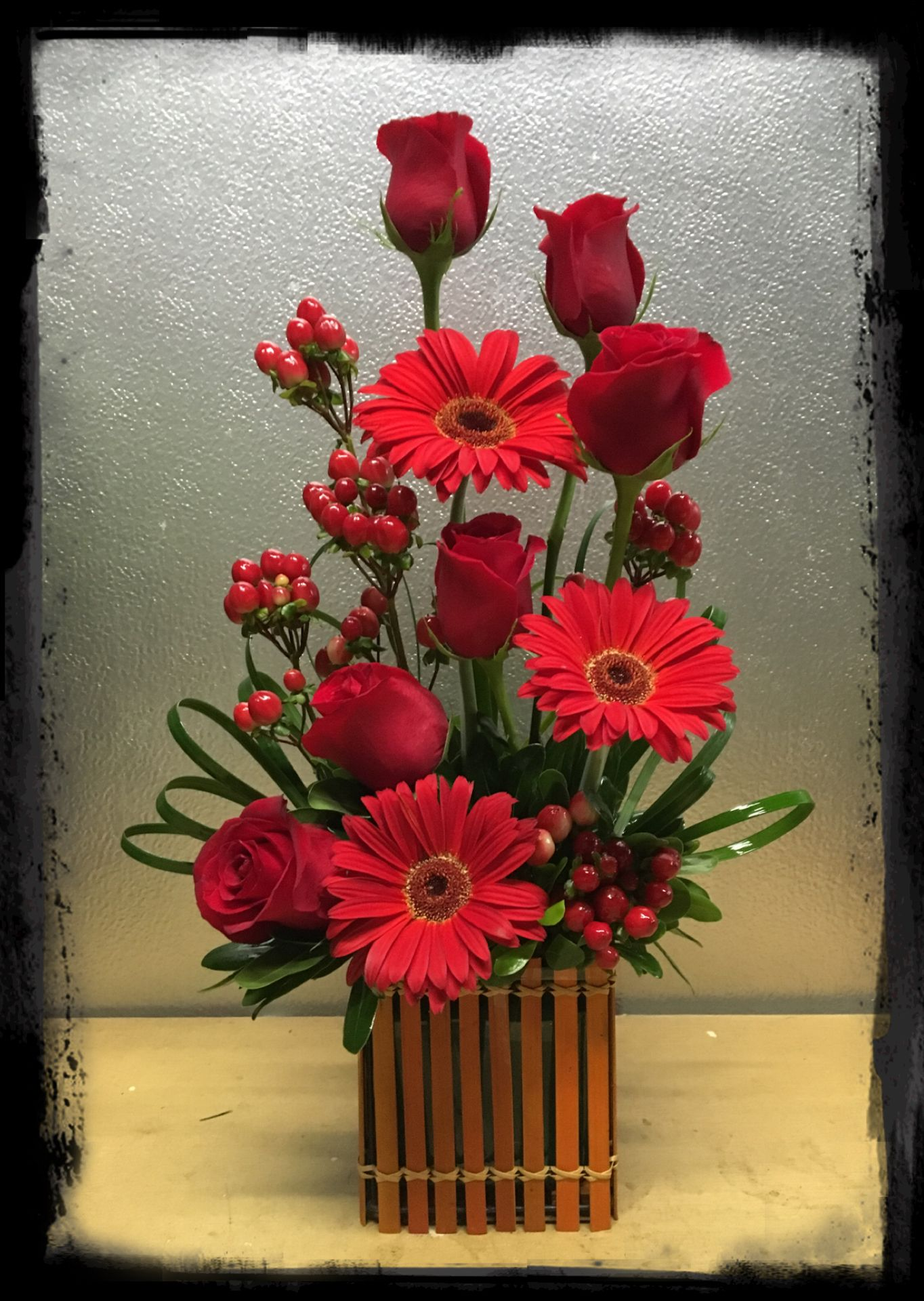 Red roses, red gerbera daisies, and hypericum floral