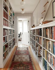 Hallway lined with bookshelves and oriental rug runner amazing design idea for book lovers also in this portland maine oceanfront cottage rh pinterest