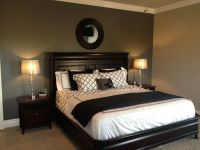 Grey accent wall with black and white bedding. Lamps ...