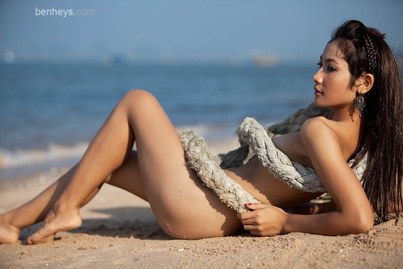 Beautiful Thai nude model wrapped in rope on beach