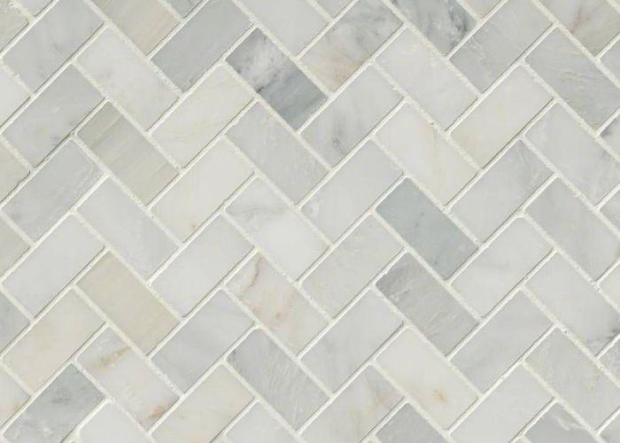 This beautiful arabescato carrara herringbone pattern honed tile is used in flooring countertops and backsplash also  mesh bathrooms