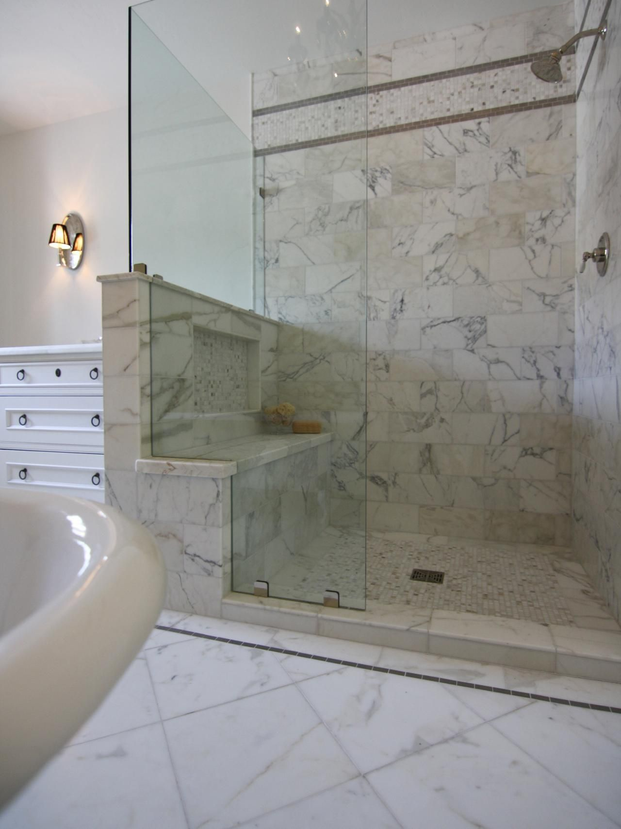 Calacatta marble enrobes this glassenclosed shower to