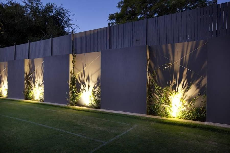 Fascinating High Concrete Fence Design With Spotlamps And Green