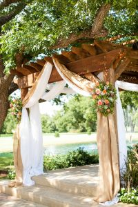 Burlap draping with country pink and green flowers over a ...