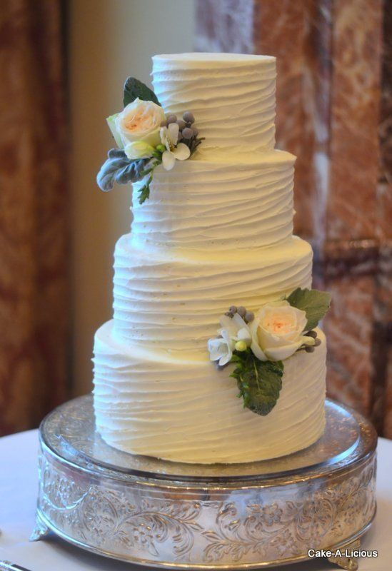 Simple 2tier cake with rippled white icing and 2 decorative flowers  10 Buttercream Wedding
