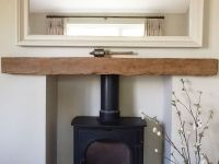A reclaimed oak beam fireplace lintel housing a wood ...