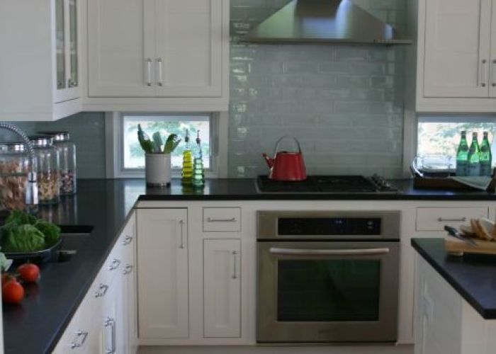 White cabinets light turquoise tiles black countertops and appliances also kitchen