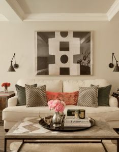 Interior designer jenny wolf shares her top tips also neutral living room sconces flanking art pillow mix home rh pinterest