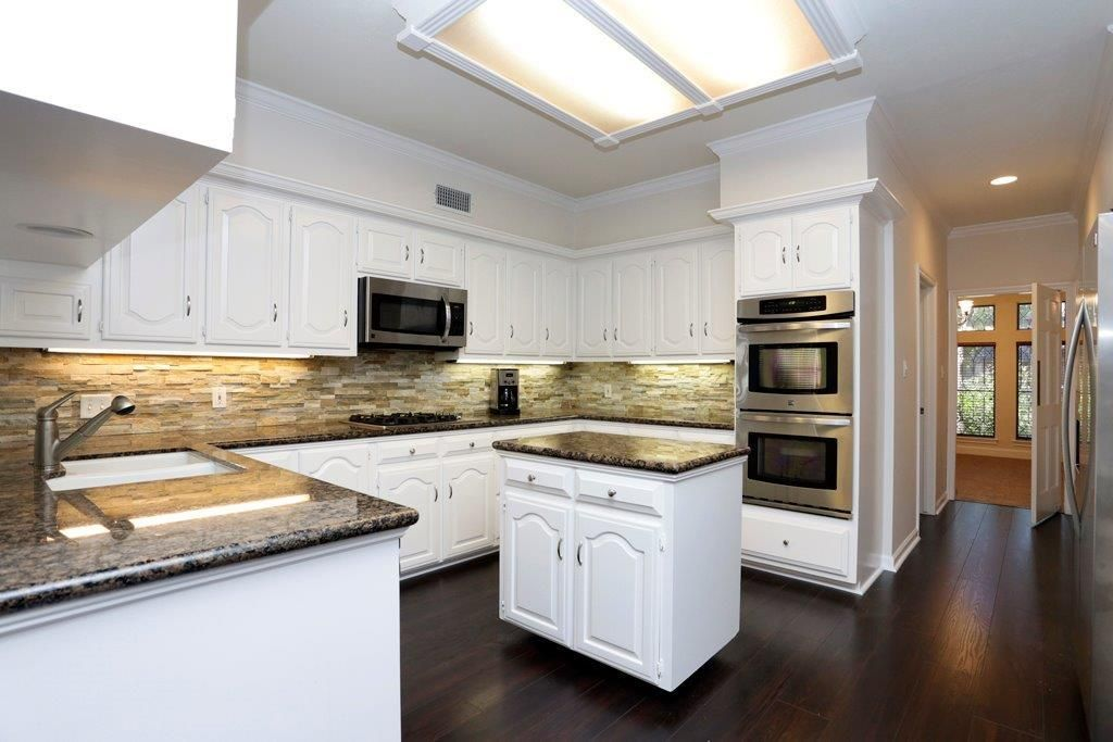 White Cabinets Stack Stone backsplash and Granite