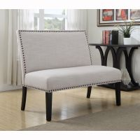 Cream upholstered banquette bench with nail head trim is