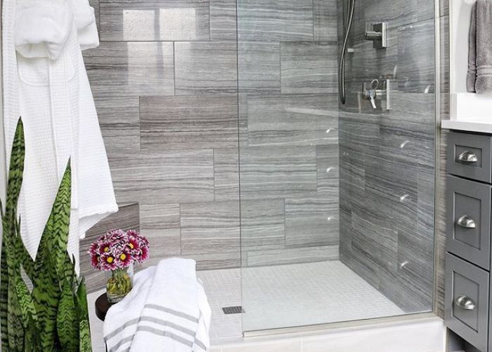 Modern bathroom with grey tile in shower and vanity also our master was typical of   homes there