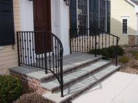 wrought iron railings curving away from the top step. i