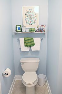 shelf, painting, and towel rack over toilet in master.