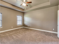 Master bedroom designed with earth tones. Tan carpeting ...