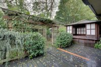 Backyard arbor next to a Japanese-style hot tub house ...