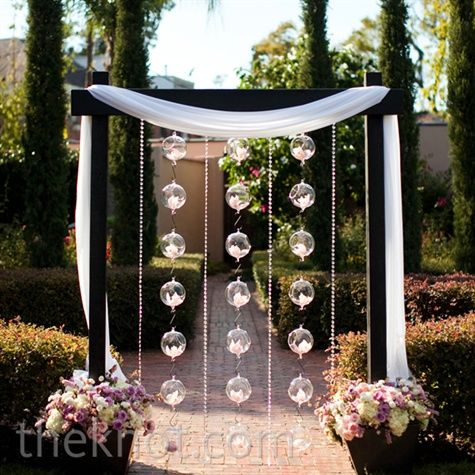 Orchid Filled Glass Balls Hung From A Wooden Arbor To Give The