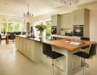 A wooden breakfast bar and granite work surfaces blend ...