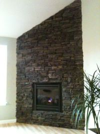 Corner drystack stone fireplace, adjacent to a vaulted ...