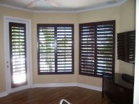 dark wood plantation shutters with yellow/brown walls and