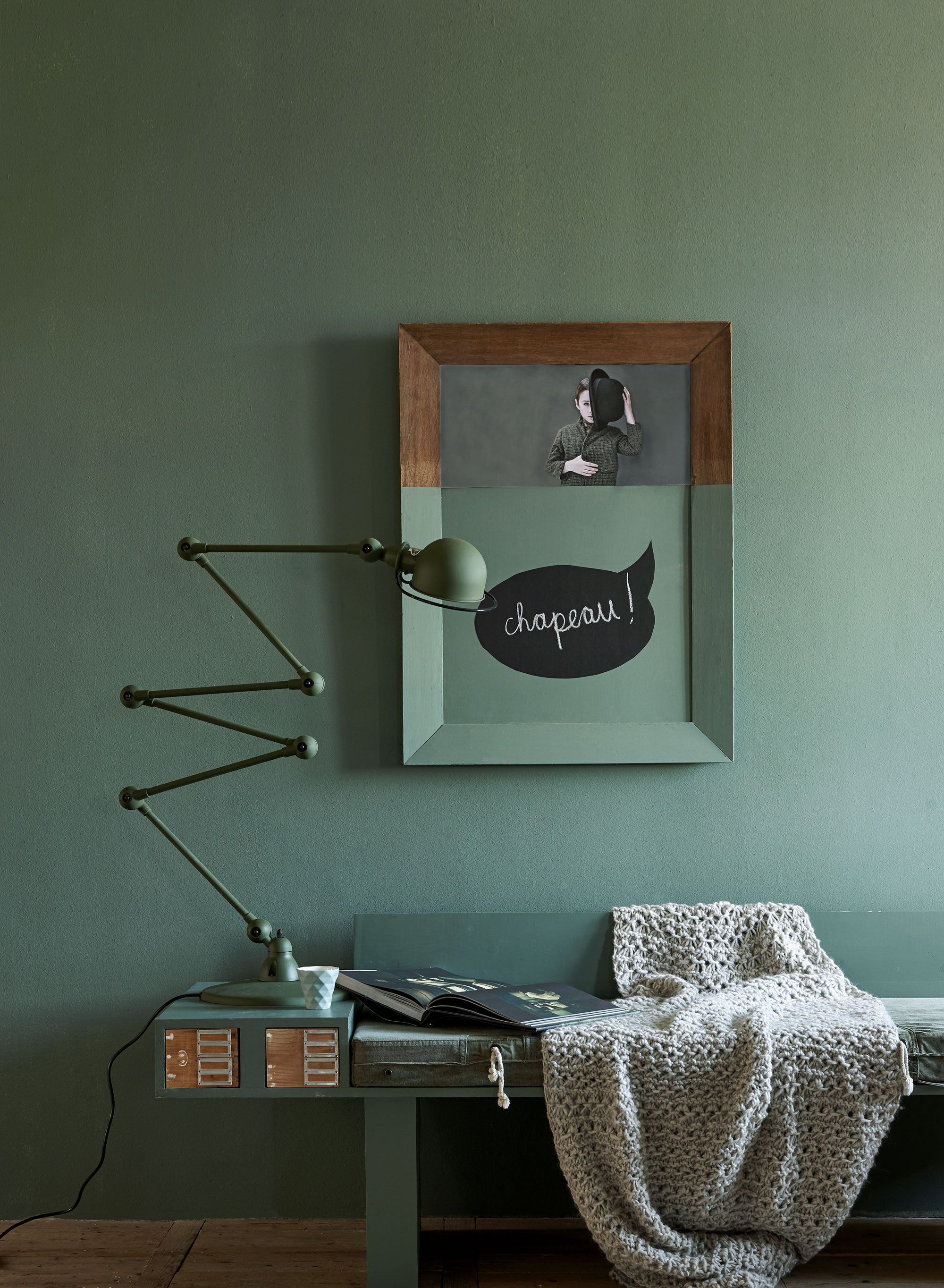 Green wall with halfpainted frame and green desk lamp