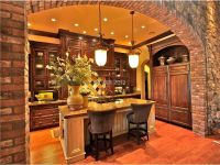 Tuscan kitchen with pendant lights and stone arch. The ...