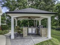 This impressive outdoor cooking area features a hip roof ...