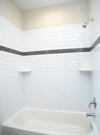 A modern style tub with subway tile surround with glass ...