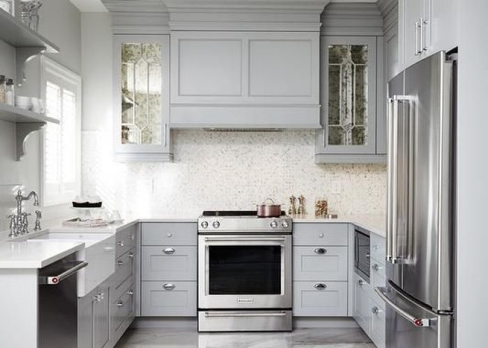 This gray  shaped kitchen features  paneled hood flanked by antiqued mirrored cabinets and mounted against white mosaic backsplash also