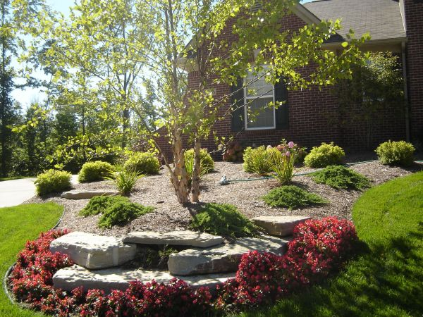red begonia flower bed with limestone