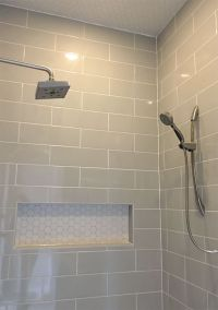 Linear light gray shower wall tile with hexagon mosaic