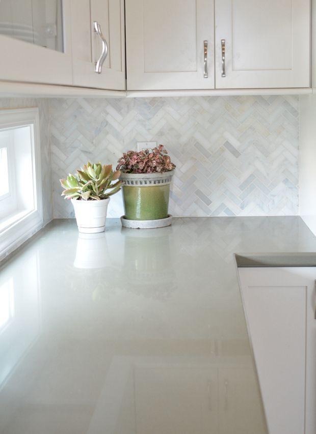 White cabinets with marble herringbone backsplash and sage