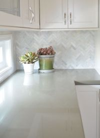 White cabinets with marble herringbone backsplash and sage