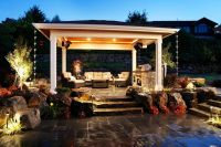 This quiet backyard patio features a covered sitting area ...