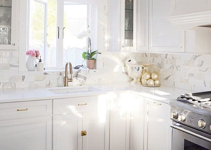 Stunning kitchen features white shaker cabinets adorned with brass pulls and glass knobs paired also