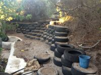 Half finished retaining wall with steps. Recycled tyres ...