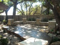 Flagstone patio with columns with a dry creek bed running ...