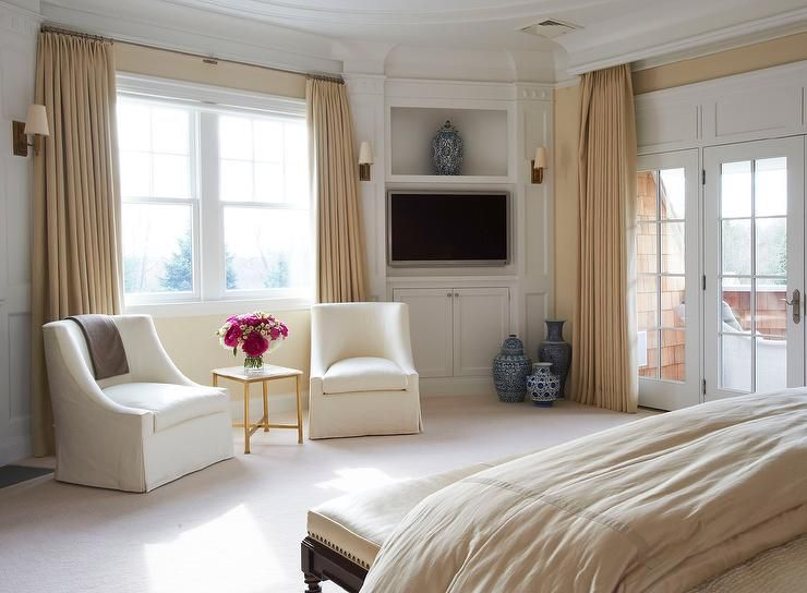 Elegant master bedroom features a bed facing a small