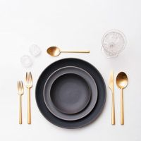 Unusal Table setting with golden cutlery & black/grey ...