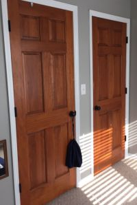 Wood stained doors, aged bronze door knobs, white trim ...