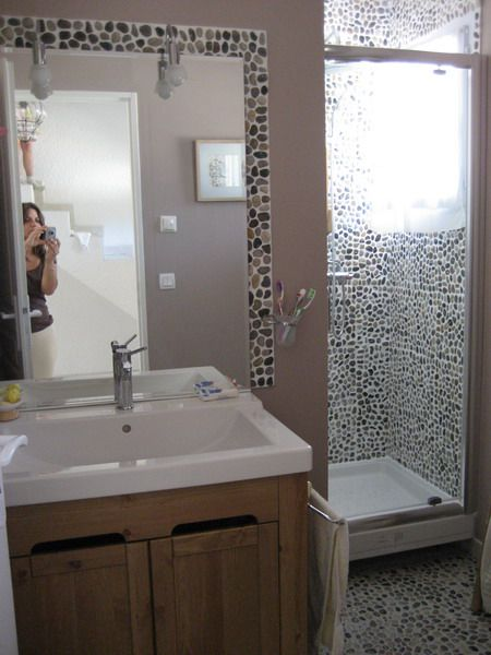Les galets sont omniprsents dans cette salle de bain  En frise au sol et au mur de la douche