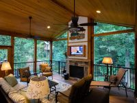 A Rustic Covered Porch with a Fireplace and TV Screen ...